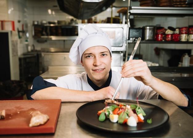 I giovani cucinano la preparazione dell'insalata con carne alla tavola Foto Gratuite