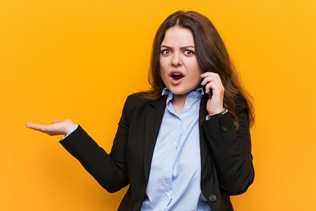 I giovani curvy più la donna di affari di dimensione che tiene un telefono ha impressionato il copyspace della tenuta sulla palma. Foto Premium