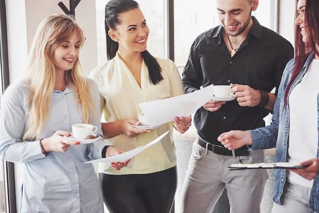 I giovani imprenditori di successo stanno parlando e sorridendo durante la pausa caffè Foto Premium