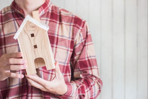 I giovani indossano la camicia rossa del percalle che tiene il modello miniatura della casa, il concetto di investimento della proprietà, copyspace Foto Premium