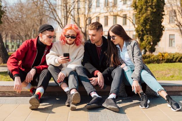 I giovani seduti sul marciapiede e guardando smartphone Foto Gratuite