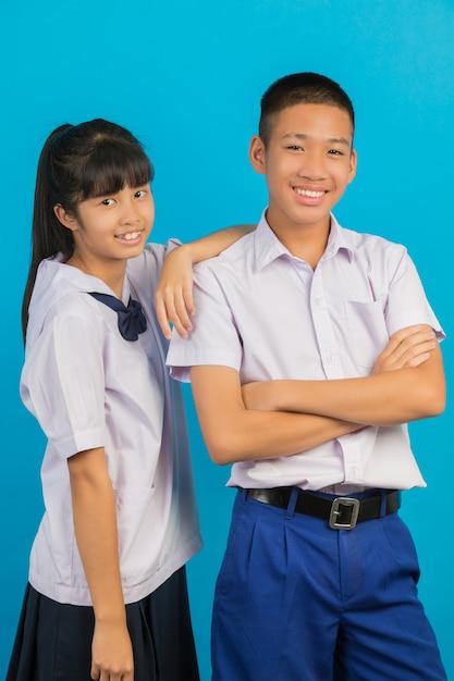 I giovani studenti asiatici e gli studenti maschi asiatici stanno insieme su un blu. Foto Gratuite