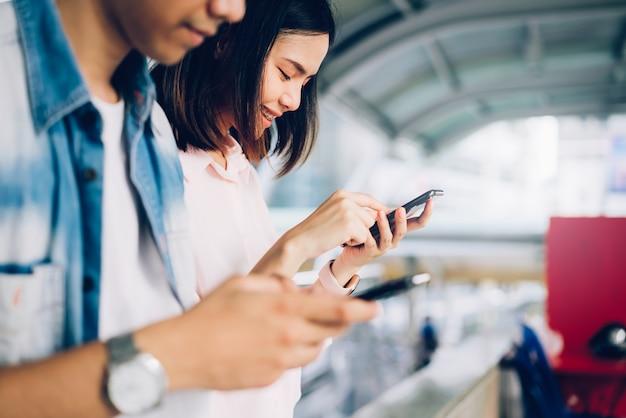 I giovani usano lo smartphone e sorridono mentre sono seduti nel tempo libero. Foto Premium