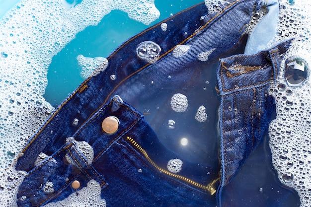 I jeans vengono immersi in soluzione di acqua detergente in polvere. concetto di lavanderia Foto Premium