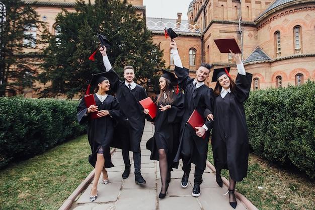 I laureati di successo in abiti accademici sono in possesso di diplomi, guardando la fotocamera e sorridendo mentre in piedi all'aperto Foto Premium
