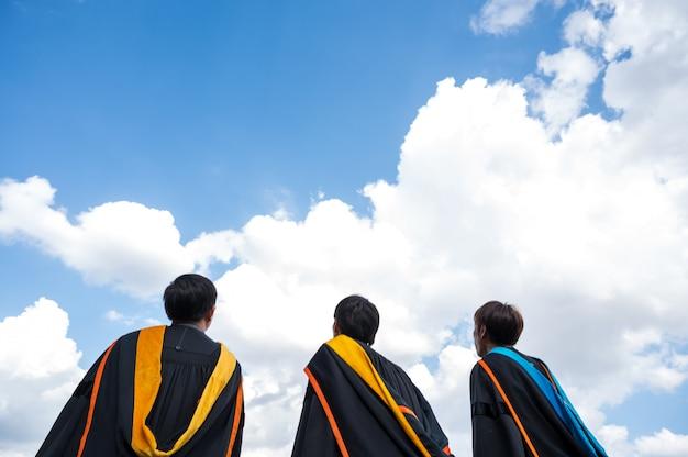 I laureati lanciano cappelli il giorno della laurea all'università. Foto Premium