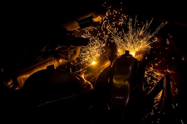 I lavoratori stanno scavando con fili di saldatura al carbonio con scintille Foto Premium