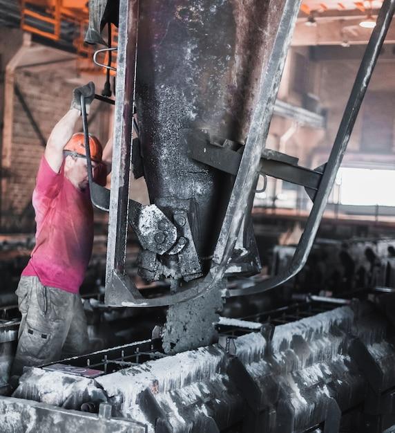 I lavoratori versano cemento bagnato nelle forme. produzione di lastre di cemento Foto Premium