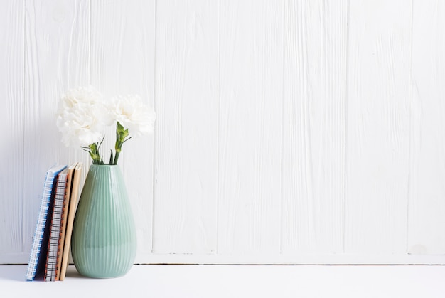 I libri si avvicinano ai fiori freschi nel vaso contro la carta da parati bianca di legno dipinta Foto Gratuite