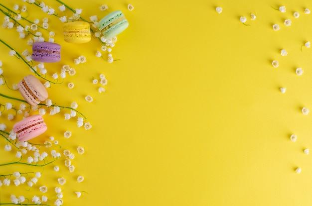 I macarons variopinti o i maccheroni decorati con i fiori di fioritura del mughetto su fondo giallo. concetto dolce dessert francese. composizione del telaio distesi. copyspace Foto Premium
