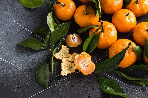 I mandarini con le foglie verdi si chiudono su su buio Foto Gratuite