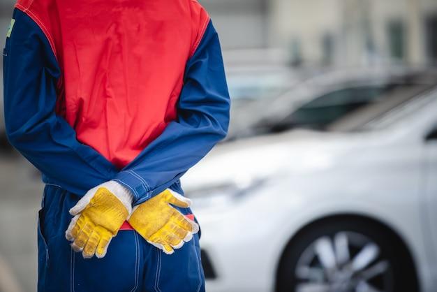 I meccanici asiatici indossano le tute da corsa per tornare nelle officine e nei centri di riparazione auto. Foto Premium