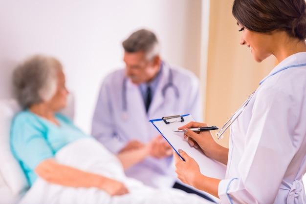 I medici sono in piedi davanti a un'anziana nonna. Foto Premium
