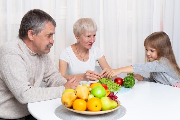 I nonni con la nipote preparano cibo sano in cucina. famiglia che prepara un'insalata insieme Foto Premium