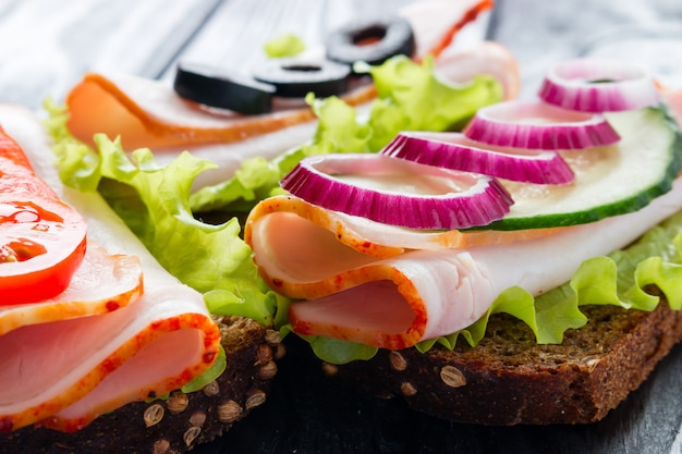 I panini con i pomodori tagliano le olive e il primo piano della cipolla rossa Foto Premium