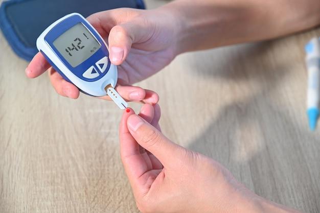 I pazienti diabetici usano un glucometro per misurare i livelli di glucosio nel sangue a casa Foto Premium