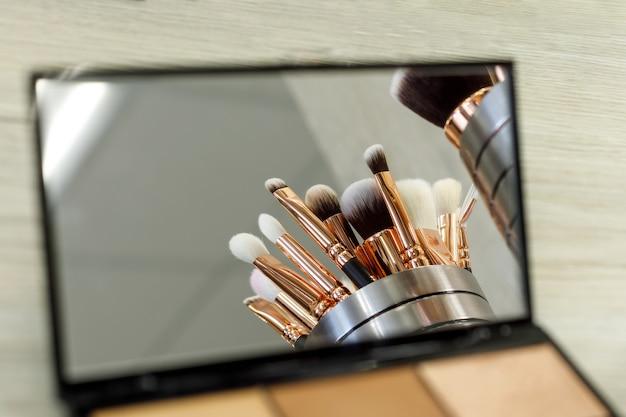 I pennelli per il trucco si riflettono in uno specchio palette con ombre Foto Premium