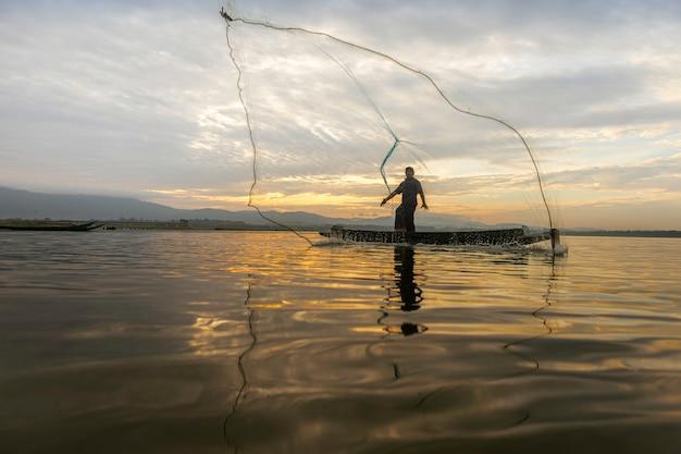 I pescatori di casting stanno andando a pescare al mattino presto con barche di legno, vecchie lanterne e reti. concetto stile di vita del pescatore. Foto Premium