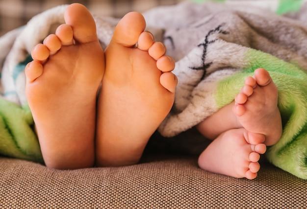I piedi dei bambini fanno capolino da sotto la coperta. due bambini di età diverse. Foto Premium