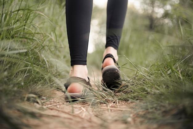 I piedi della donna sulla strada sterrata erbosa Foto Gratuite