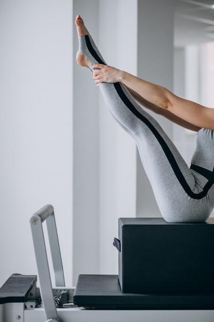 I pilates di pratica della donna in un riformatore dei pilates si chiudono su Foto Gratuite