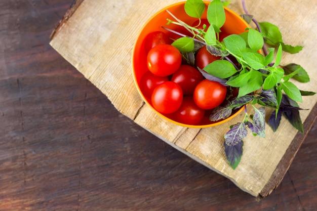 I pomodori maturi freschi, il basilico verde e viola leavesin una ciotola su un tagliere di legno Foto Premium