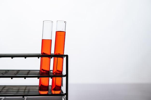 I prodotti chimici arancioni in un tubo di vetro di scienza hanno organizzato su una mensola Foto Gratuite