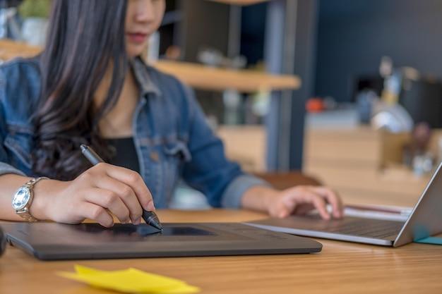 I progettisti grafici lavorano con i prodotti e i siti web di progettazione di penne e computer Foto Premium