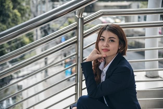 I ritratti di bella donna asiatica sembrano allegri e la fiducia è seduta all'aperto Foto Premium