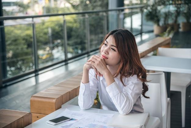 I ritratti di bella donna asiatica sembrano allegri e la fiducia è seduta e sente il successo con il lavoro. Foto Premium