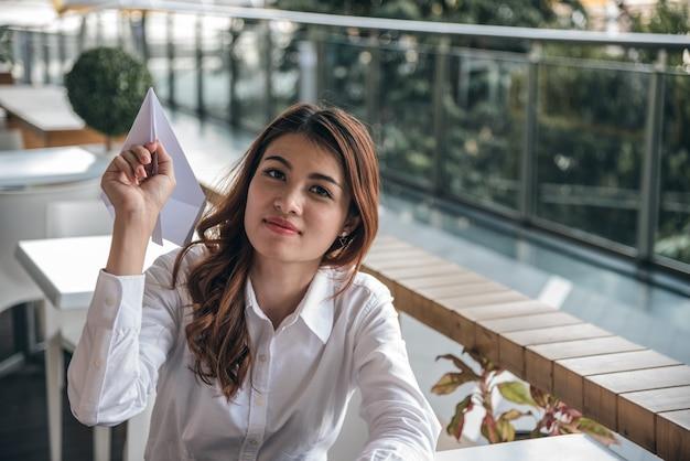 I ritratti di bella fiducia asiatica di sguardo della donna è stanti e tenenti l'aereo di carta Foto Premium