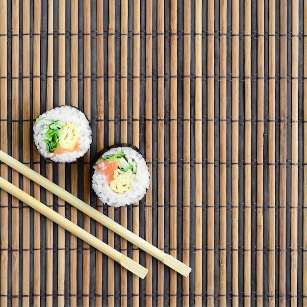 I rotoli di sushi e le bacchette di legno si trovano su una stuoia di paglia di bambù Foto Premium