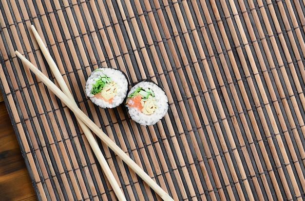 I rotoli di sushi e le bacchette di legno si trovano su una stuoia di paglia di bambù. Foto Premium