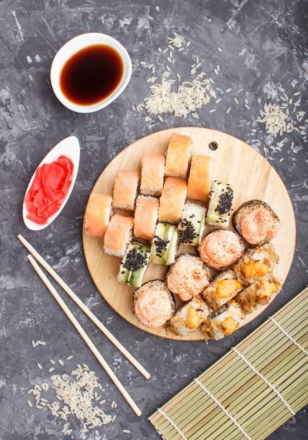 I rotoli di sushi giapponesi misti di maki hanno messo con le bacchette, lo zenzero, la salsa di soia, il riso, vista superiore. Foto Premium
