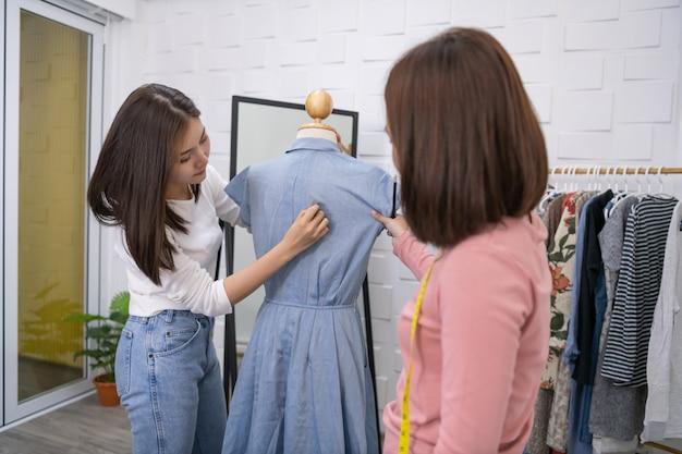 I sarti stanno aiutando a lavorare seriamente. la giovane donna sta progettando vestiti nella stanza. Foto Premium