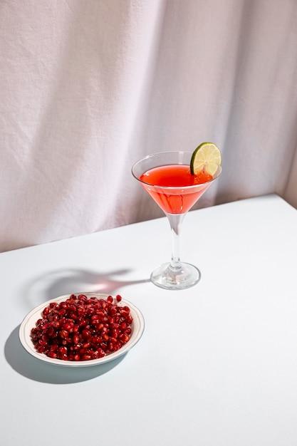 I semi maturi rossi del melograno con il cocktail bevono sullo scrittorio bianco Foto Gratuite