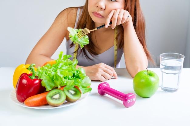 I sintomi dell'anoressia si manifestano nell'avversione al cibo. ritratto di giovane donna asiatica in espressione emotiva facciale insoddisfatta, rifiutando di mangiare veterinari e frutta. avvicinamento Foto Premium