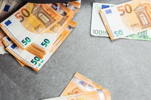 I soldi. contanti in euro. banconote in euro. mucchio di banconote in euro di carta come parte del sistema di pagamento del paese unito 50 100 200. cinquanta, cento e duecento euro. sfondo. Foto Premium