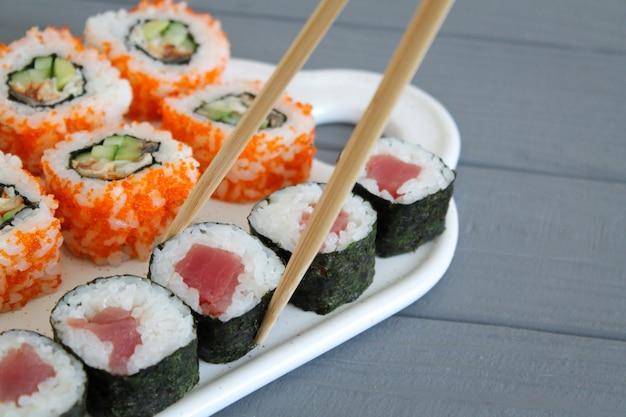 I sushi hanno messo con le bacchette sulla tabella di legno grigia Foto Premium