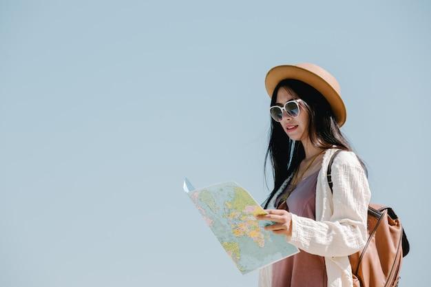 I turisti femminili a disposizione hanno una mappa di viaggio felice. Foto Gratuite