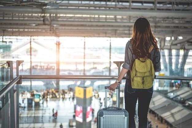 I turisti femminili di bellezza che aspettano il volo per decollare all'aeroporto. persone e stili di vita Foto Premium