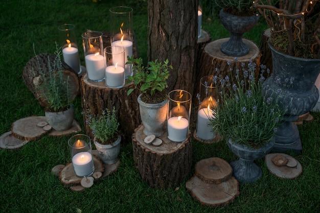 I vasi alti con candele bianche si levano in piedi sui blocchi del giardino Foto Gratuite