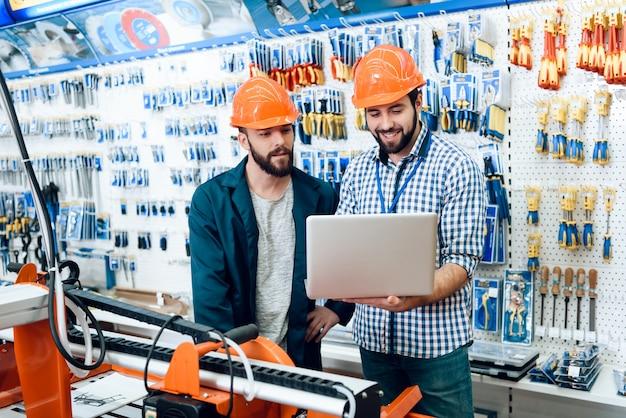 I venditori stanno lavorando nel negozio di utensili elettrici Foto Premium