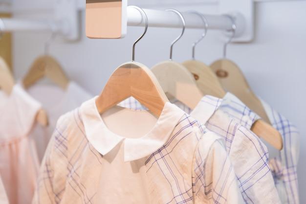 I vestiti appendono su una mensola in un negozio di vestiti firmati a melbourne, in australia Foto Premium