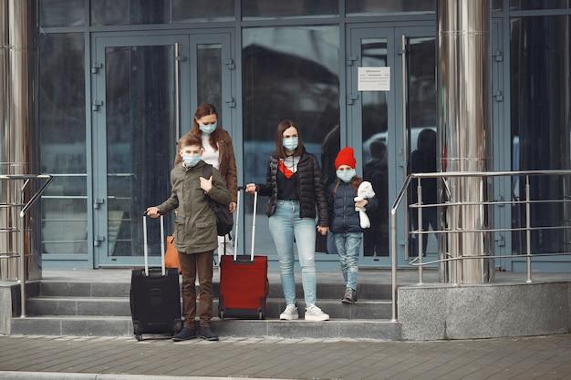 I viaggiatori che lasciano l'aeroporto indossano maschere protettive Foto Gratuite