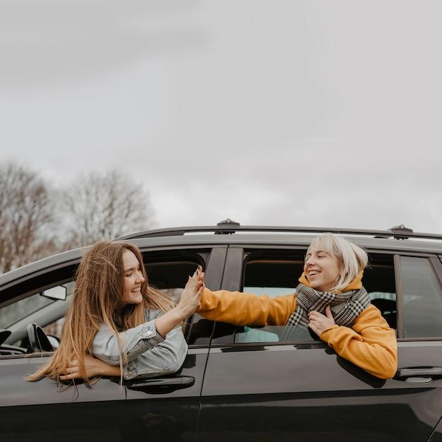 I viaggiatori festeggiano fuori dal finestrino della macchina Foto Gratuite
