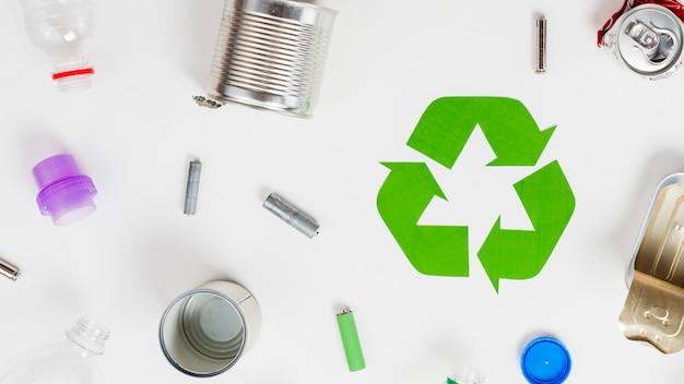 Icona di riciclaggio intorno a diversi rifiuti Foto Gratuite