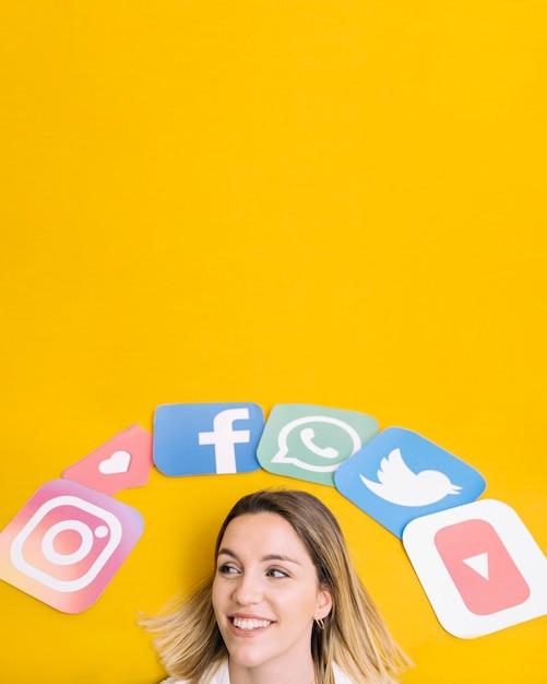 Icone dell'applicazione sociale di media sopra la testa della donna felice sul contesto giallo Foto Gratuite