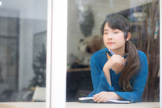 Idea di pensiero sorridente e scrittura del bello giovane scrittore asiatico della donna del ritratto sul taccuino Foto Premium