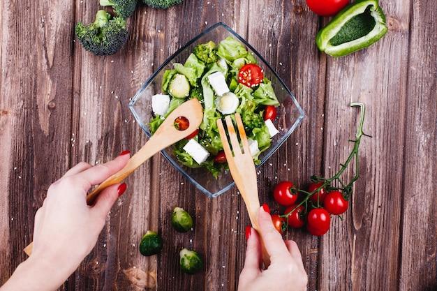 Idee per il pranzo o la cena la donna scuote l'insalata fresca di verde, avocado, peperone verde Foto Gratuite